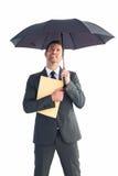 Businessman sheltering under umbrella holding file Royalty Free Stock Photography