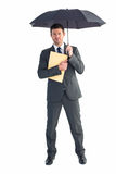 Businessman sheltering under umbrella holding file Royalty Free Stock Images