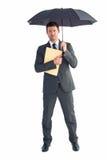 Businessman sheltering under umbrella holding file Royalty Free Stock Images