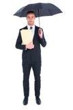 Businessman sheltering under umbrella holding file Royalty Free Stock Photos