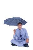 Businessman sheltering under umbrella Stock Photography