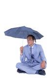 Businessman sheltering under umbrella Royalty Free Stock Images