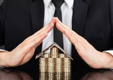 Businessman Shielding House Made Of Money At Desk Royalty Free Stock Photography