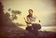 Businessman Shipwrecked on a desert island. With message in a bottle Royalty Free Stock Image