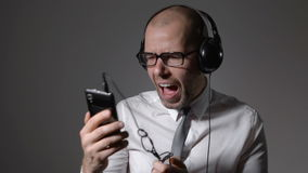 Businessman in a shirt and big headphones, singing in a smartphone, uses an application. stock video footage