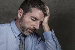 Businessman in shirt and necktie suffering depression problem feeling tired and overwhelmed isolated on grunge background in royalty free stock image