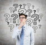 Businessman in shirt thinking. And drawing question marks on wall Royalty Free Stock Photography