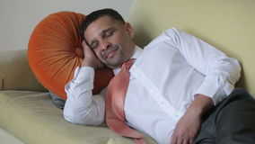 Businessman in shirt and tie resting and yawning on a couch stock video footage