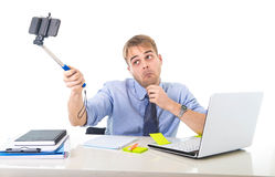 Businessman in shirt and tie sitting at office computer desk holding selfie stick shooting self portrait photo. Young businessman in shirt and tie sitting at Royalty Free Stock Images