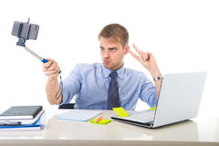 Businessman in shirt and tie sitting at office computer desk holding selfie stick shooting self portrait photo. Young businessman in shirt and tie sitting at Royalty Free Stock Photography