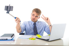 Businessman in shirt and tie sitting at office computer desk holding selfie stick shooting self portrait photo Royalty Free Stock Images