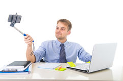 Businessman in shirt and tie sitting at office computer desk holding selfie stick shooting self portrait photo. Young businessman in shirt and tie sitting at Stock Image
