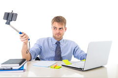 Businessman in shirt and tie sitting at office computer desk holding selfie stick shooting self portrait photo stock photos