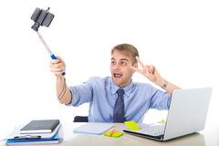 Businessman in shirt and tie sitting at office computer desk holding selfie stick shooting self portrait photo Royalty Free Stock Photography