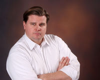 Businessman in shirtsleeves. Looking at the camera, this businessman has a very stern expression Stock Image