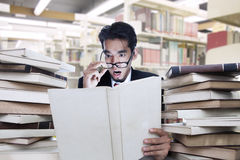 Businessman shock looking at book. Businessman looking a white book on shock at the library Stock Photo
