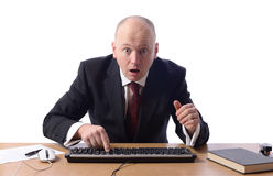 Businessman shocked. Surprised businessman sat at desk looking at computer screen isolated on white Royalty Free Stock Photography
