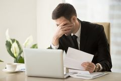 CEO shocked because refusal to renew work contract. Businessman shocked with bad news in letter, upset because of loan refusal, feeling suppressed when receiving Stock Photo