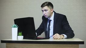 Businessman is shocked by laptop breakdown, smoke comes from computer stock footage