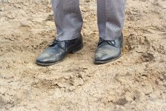 Businessman shoes. Businessman walk on clay. Dirty shoes Stock Image
