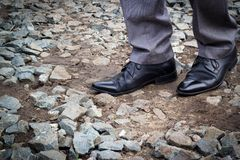 Businessman shoes. Businessman walk on rubble and gravel Stock Photos