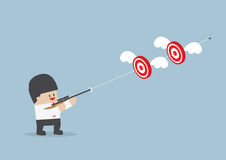Businessman shoot two targets with one bullet Royalty Free Stock Photography
