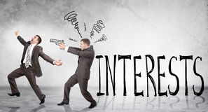 Businessman shooting  another man. With word interests on grey wall background Royalty Free Stock Photos