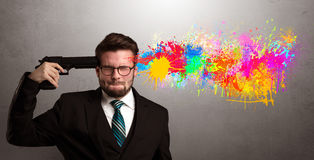 Businessman shooting his head with gun. Man shoots his head with gun and colorful splotch are coming out from his head Stock Photos