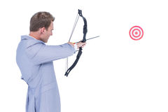 Businessman shooting target with arrow and bow Stock Image