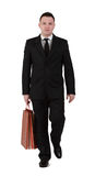 Businessman shopping. Young businessman with shopping bag walking against a white background Royalty Free Stock Images