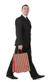 Businessman shopping. Young businessman with shopping bag walking against a white background Stock Image