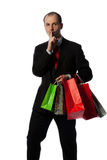 Businessman with shopping bags, making quiet sign Stock Images