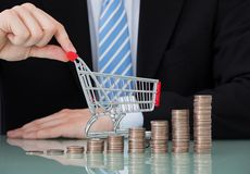 Businessman with shopping cart and coin stacks in office Stock Images