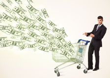 Businessman with shopping cart with dollar bills Royalty Free Stock Photography