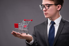 The businessman with shopping cart on gray background Stock Images