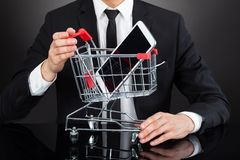 Businessman With Shopping Cart Model And Mobile Phone At Desk Stock Images