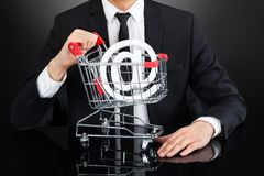 Businessman with shopping cart model and at sign at desk Royalty Free Stock Photography