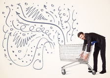 Businessman with shopping cart Royalty Free Stock Photography