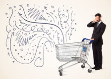 Businessman with shopping cart. Businessman pushing a shopping cart curly lines, arrows coming out of it Stock Photo
