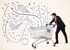 Businessman with shopping cart. Businessman pushing a shopping cart curly lines, arrows coming out of it Stock Image