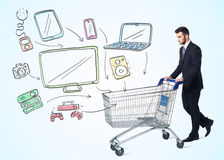 Businessman with shopping cart. Businessman pushing a shopping cart drawn media devices coming out of it Stock Photos