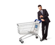 Businessman with shopping cart. Businessman pushing a shopping cart on isolated background Stock Image