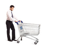 Businessman with shopping cart. Businessman pushing a shopping cart on isolated background Royalty Free Stock Photos