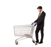 Businessman with shopping cart. Businessman pushing a shopping cart on isolated background Stock Images