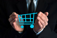 Businessman with a shopping cart symbol Stock Images