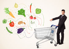 Businessman with shopping cart with vegetables. Businessman pushing a shopping cart and healthy vegetables coming out of it Royalty Free Stock Image