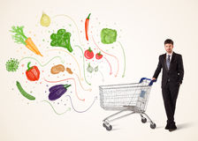 Businessman with shopping cart with vegetables. Businessman pushing a shopping cart and healthy vegetables coming out of it Royalty Free Stock Photos