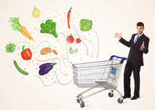 Businessman with shopping cart with vegetables. Businessman pushing a shopping cart and healthy vegetables coming out of it Royalty Free Stock Images