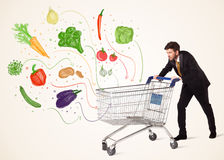 Businessman with shopping cart with vegetables. Businessman pushing a shopping cart and healthy vegetables coming out of it Stock Photography