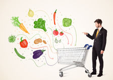 Businessman with shopping cart with vegetables. Businessman pushing a shopping cart and healthy vegetables coming out of it Stock Photo
